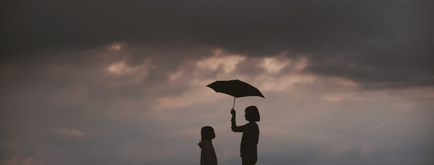 Woman and child with umbrella - Photo by J W on Unsplash